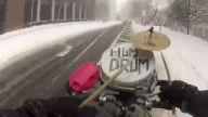 Karlı yolda bisiklet üzerinde davul çalmak